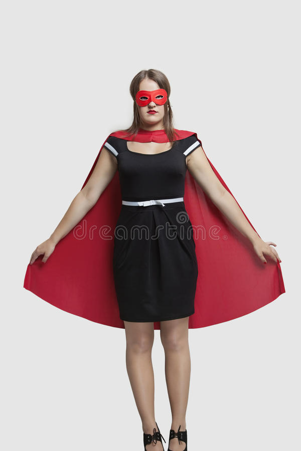 Young woman standing in superhero costume over gray background stock images