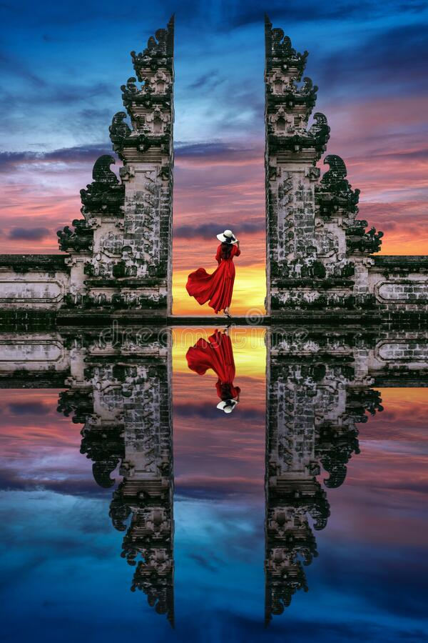 Young woman standing in temple gates at Lempuyang Luhur temple in Bali, Indonesia stock photo