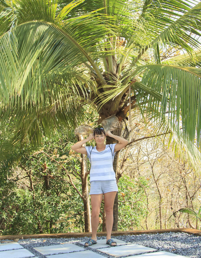 Young woman standing under a palm tree with two leaves stock images