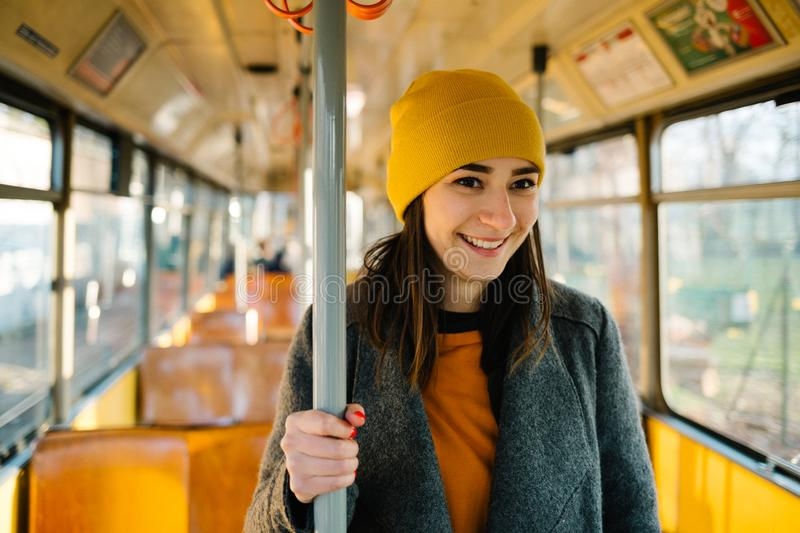 Young woman standing in a wagon of a driving tramway. Transportation, travel and lifestyle concept stock photo