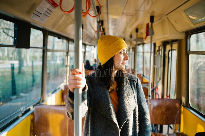 Young woman standing in a wagon of a driving tramway. Transportation, travel and lifestyle concept royalty free stock photos