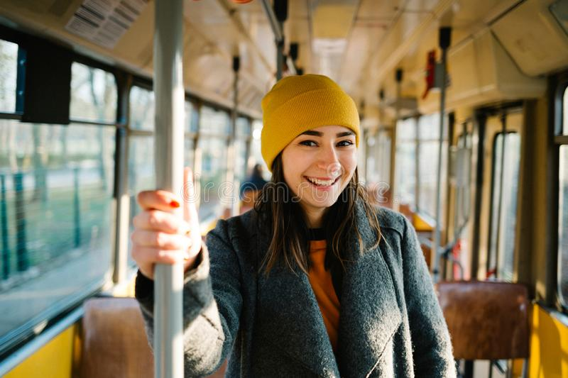 Young woman standing in a wagon of a driving tramway. Transportation, travel and lifestyle concept stock photography