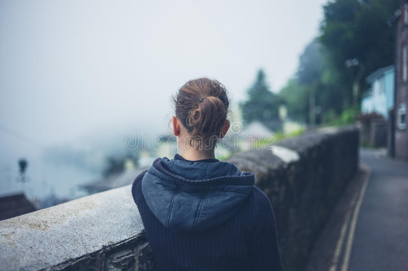 Young woman standing by wall in fog. A young woman is standing by a wall outside on a foggy day stock image