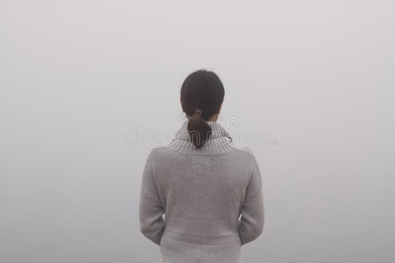 Young woman is standing by the water on a foggy day. Woman is standing by the water on a foggy day stock photography