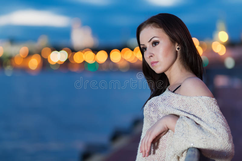 A young woman is standing on the waterfront stock photo