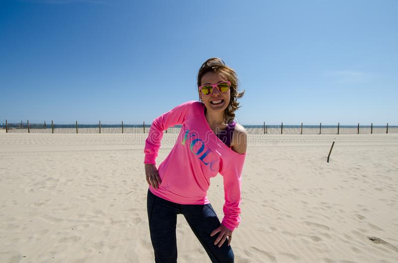Young woman stands on the beach, wearing a neon pink YOLO shirt with sunglasses, as her hair blows in the wind.  stock photography