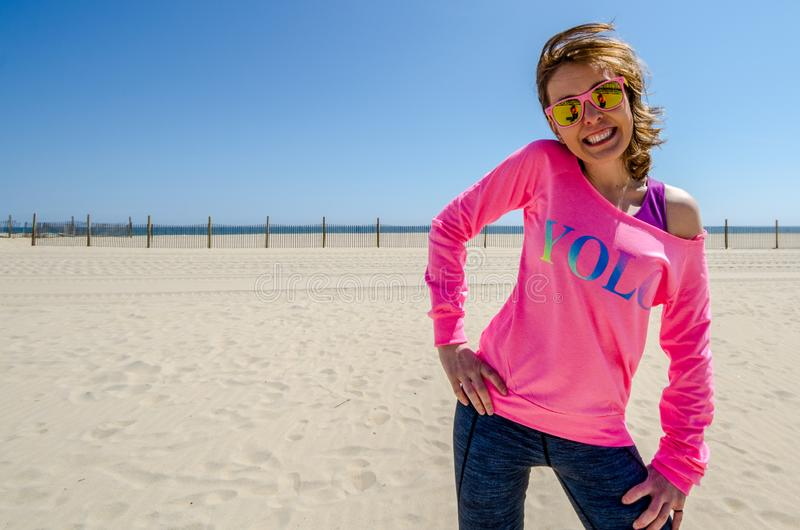 Young woman stands on the beach, wearing a neon pink YOLO shirt with sunglasses, as her hair blows in the wind.  stock photos