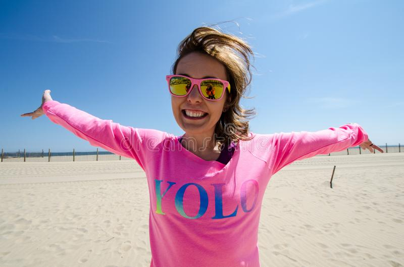 Young woman stands on the beach, wearing a neon pink YOLO shirt with sunglasses, as her hair blows in the wind.  royalty free stock images