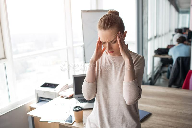 Young woman stands in a big office room and keeping her hands close to the head. She has a headache. It is a strong pain stock photo
