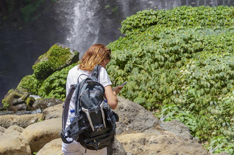 A young woman stands with her back in white clothes with a backpack at the Sekumpul Great Waterfall in the deep rainforest of Bali. A young woman stands with her stock photos
