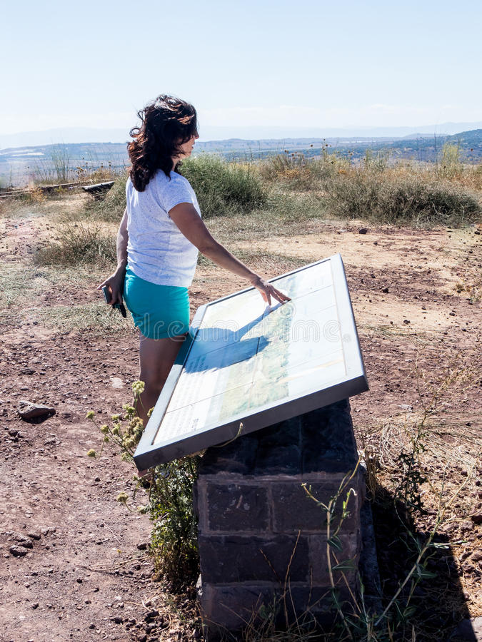 A young woman stands on a hill and examines a map of the Golan Heights stock photography