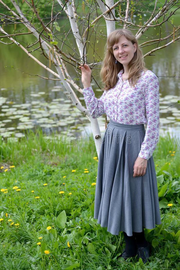 The young woman stands near the blossoming birch of useful Himalaya Betula utilis D. Don. On the bank of a pond royalty free stock image