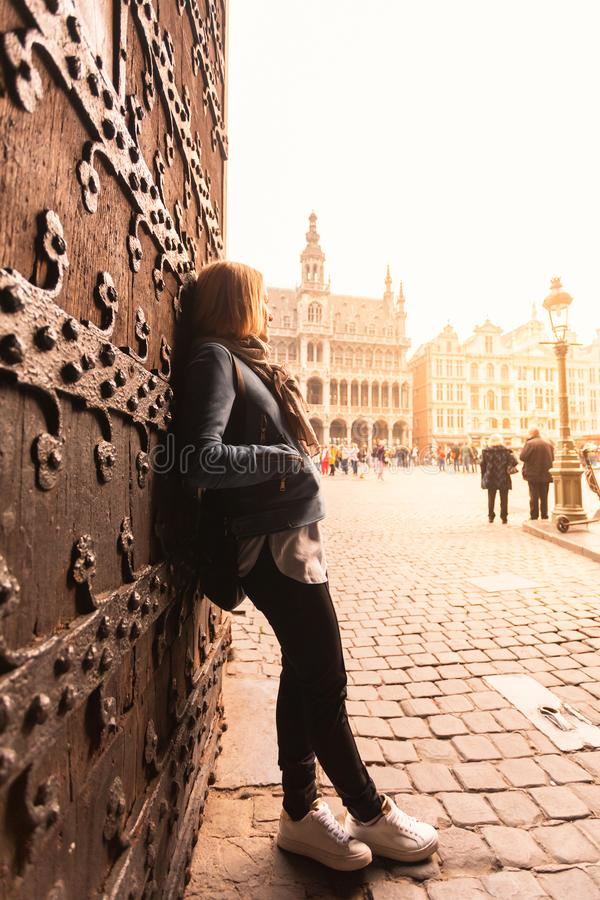 A young woman stands near the old gate in the heart of Brussels and looks at the King house and the Grand Place at. Sunset. Nice orange toning royalty free stock photo