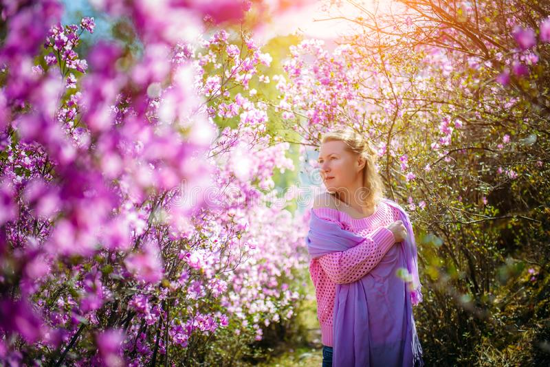 Young woman stands, resting and enjoying the spring blooming garden among the rhododendron flowers in the sunlight royalty free stock image