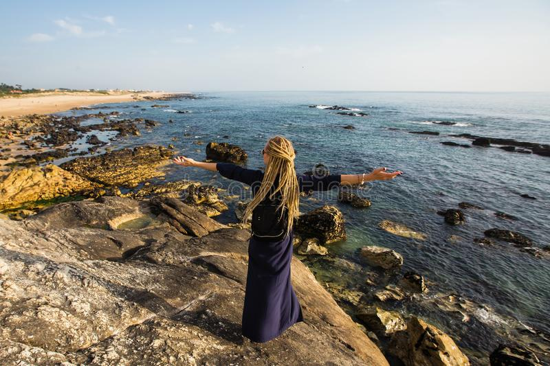 A young woman stands on the rocky shore of the ocean watching the surf stock images