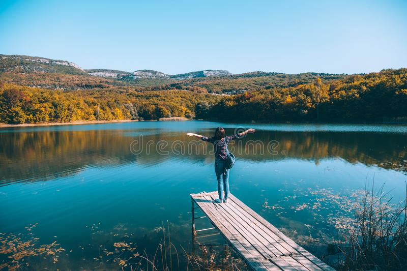 Person sitting on peer by the lake stock photo