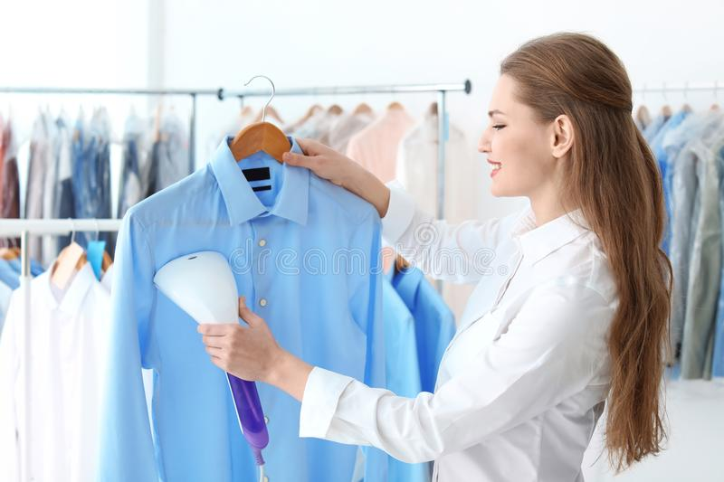 Young woman steaming shirt. At dry-cleaner`s stock photo