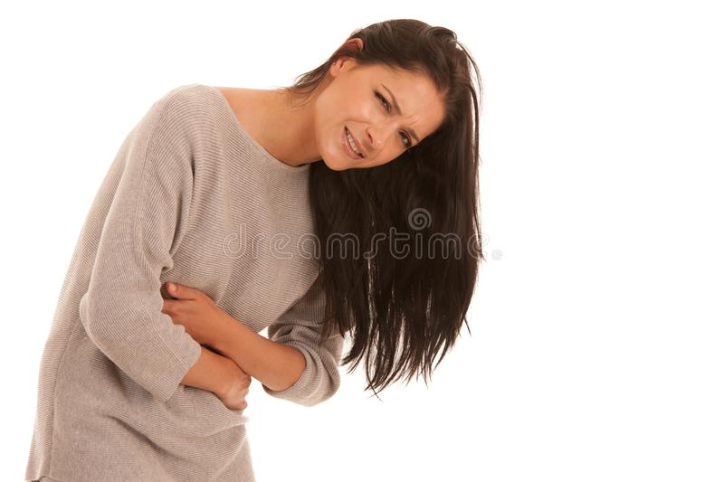 Young woman with stomach ache suffering isolated over white back royalty free stock image