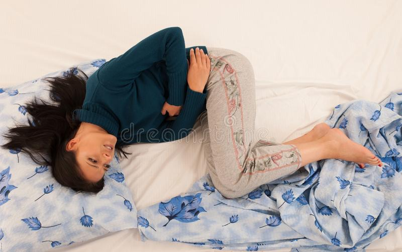 Young woman with stomach ache suffering over white back stock images