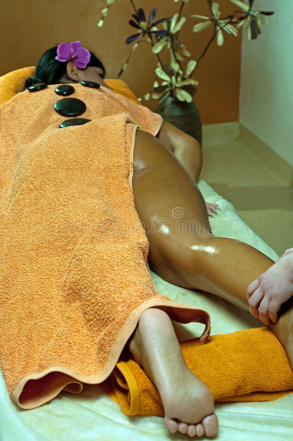 Young Woman and Stone Massage royalty free stock image