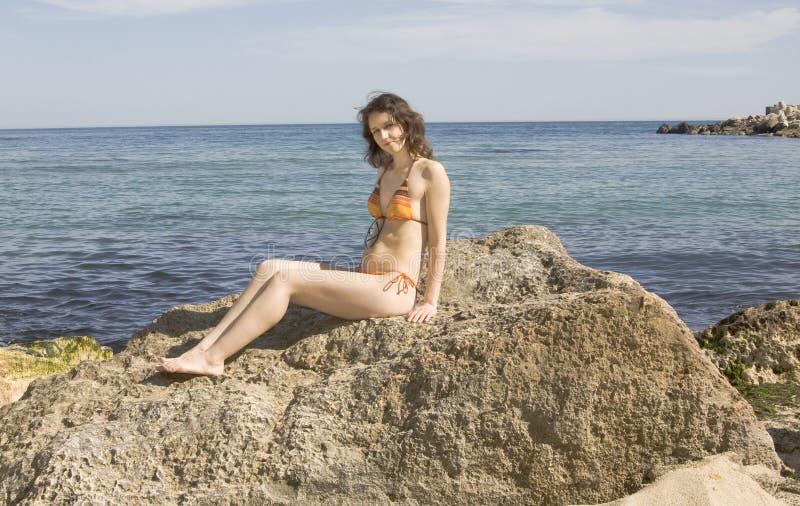 Young woman on stone on sea. Young European woman in bikini with brown hair sit on big stone on seashore royalty free stock photo