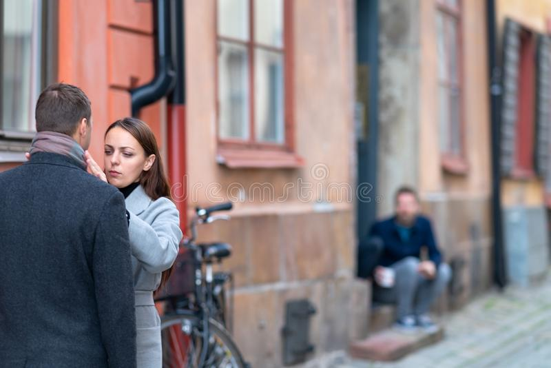 Young woman straightening her husbands clothing stock photography
