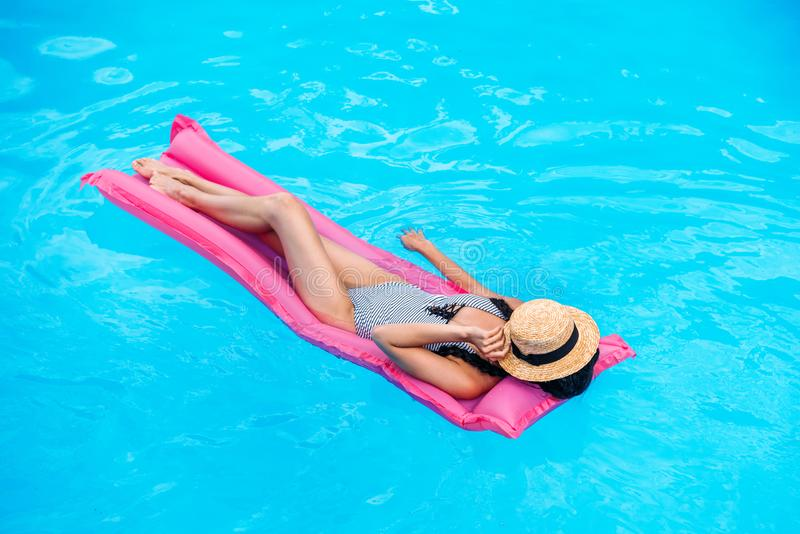 Young woman with straw hat covering face floating on air mattress royalty free stock images