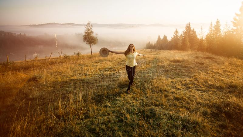 Young woman in straw hat walk in morning on top of hill with mountains background. Harmony with nature royalty free stock photography