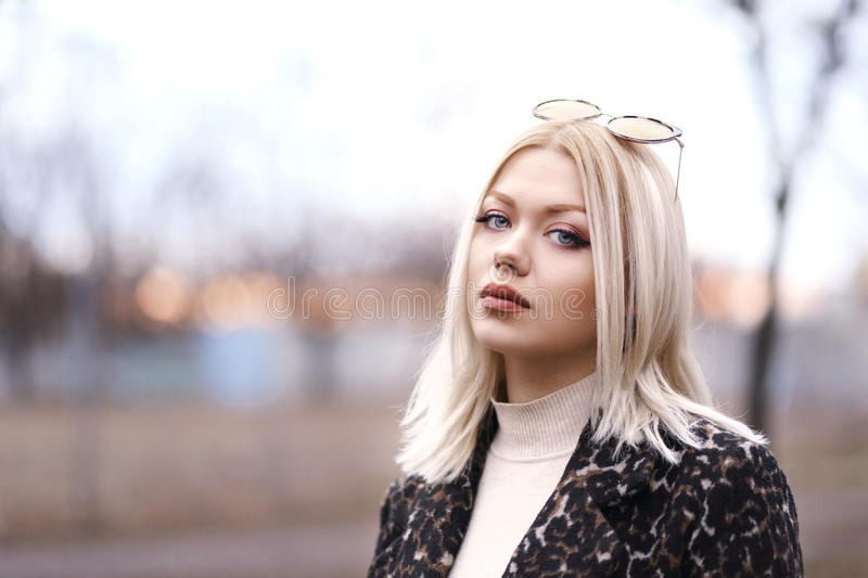Young woman on the street. Half length portrait of young beautiful blond woman walking in the park in sunset royalty free stock photo