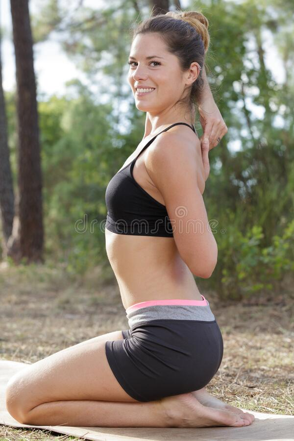 Young woman stretching arm on yoga met outdoors at sunset stock photo