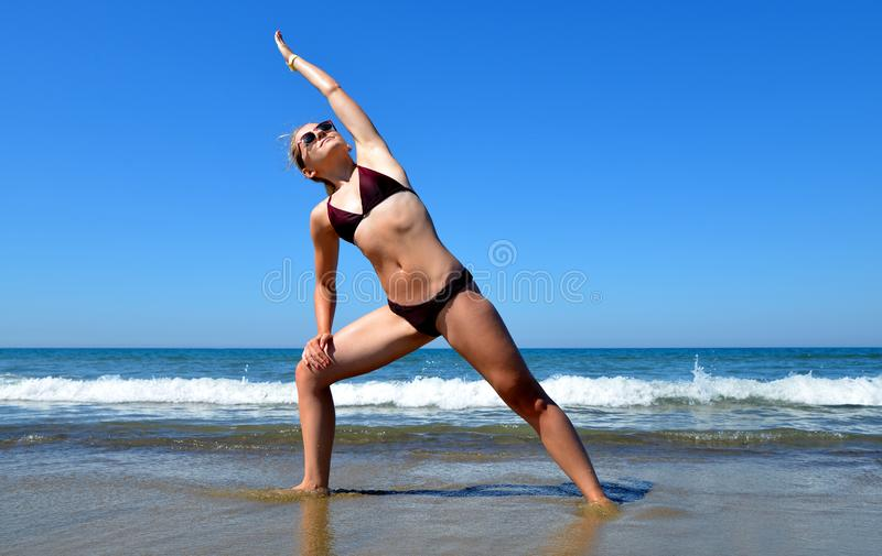 Young woman stretching body on a sandy beach. royalty free stock images
