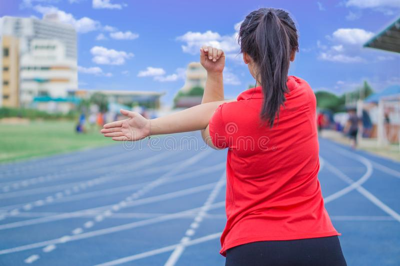 Young woman stretching her arms before running and exercising on running tracks. Young woman warming up outdoors. Sport and stock photo