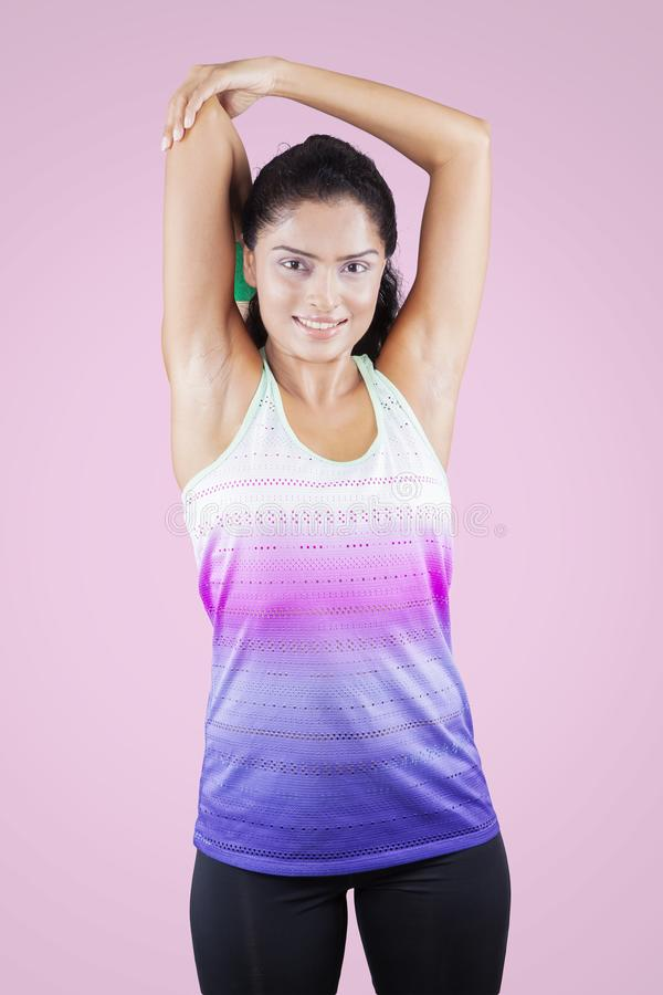 Young woman stretching her arms while smiling royalty free stock photo