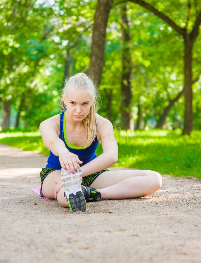 Young woman stretching legs before run royalty free stock photography