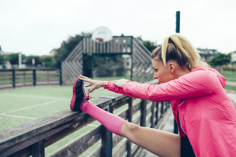 Young woman stretching legs before training outdoors royalty free stock photos