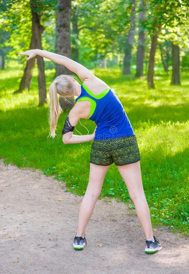 Young woman stretching the muscles of her arms and back before jogging royalty free stock photography