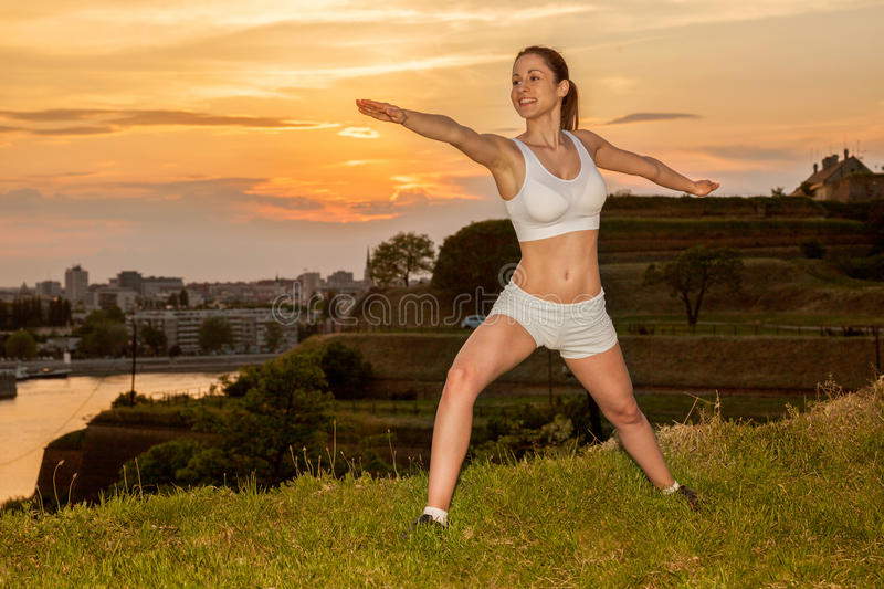 Young woman stretching outdoor in sunset stock image