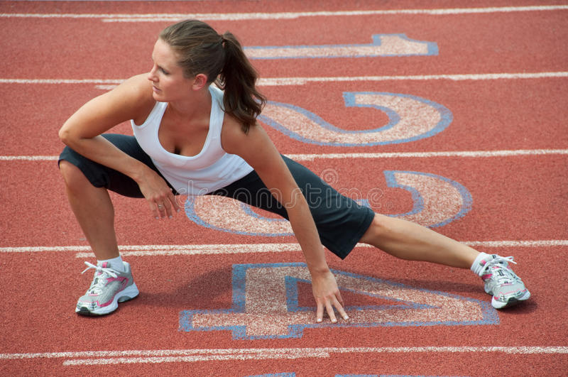 Young Woman Stretching on Running Track stock photos
