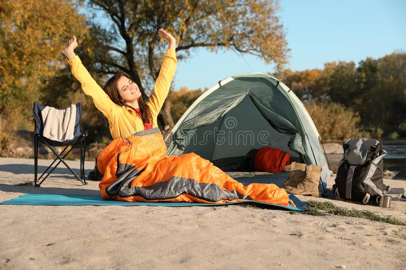 Young woman stretching in sleeping bag near camping tent royalty free stock images
