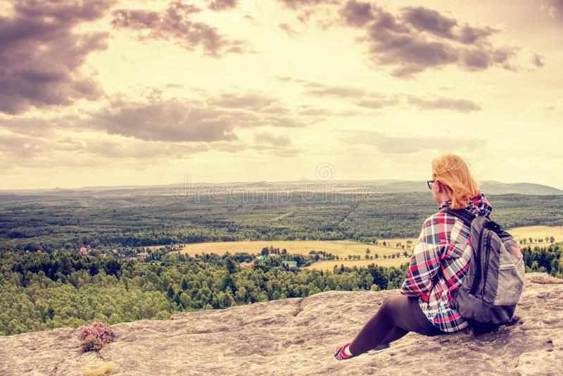 Young woman in striped jacket take a rest on rocky summit royalty free stock image