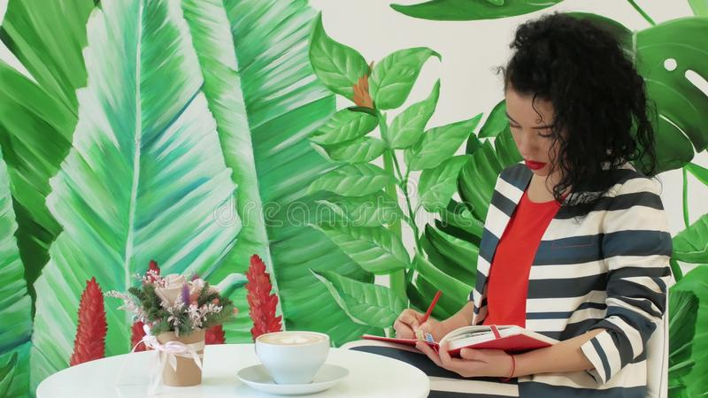 Young woman in a striped suit takes notes with a pencil in a red notepad. Against the background of drawn green leaves. Girl writer creates a new work in a cafe royalty free stock image