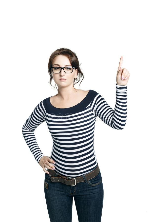 A young woman in a striped tight blouse and round glasses shows a gesture right arm lifted a finger up and looks strictly. stock image