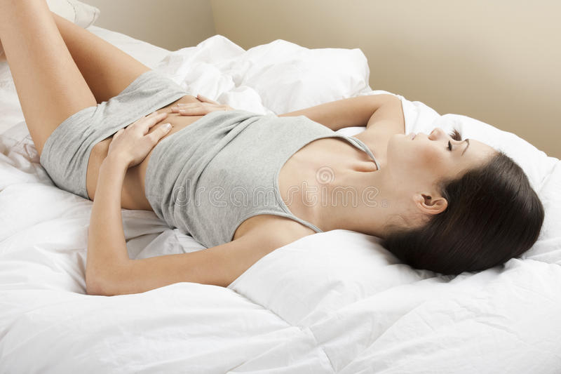 Young woman stroking her belly. Bellyache or constipation stock images