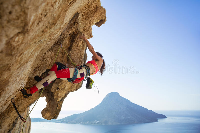 Young woman struggling to climb overhanging cliff. Against view of sea and island royalty free stock photos
