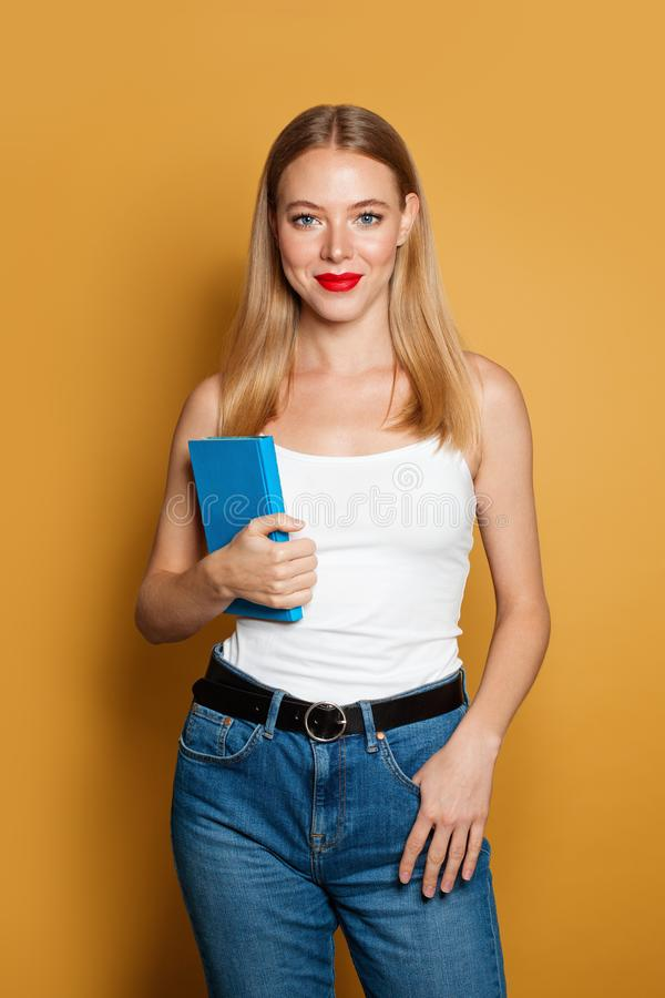 Young woman student holding blue book on bright yellow background stock image
