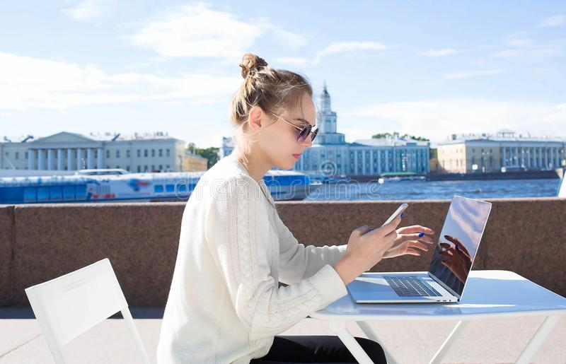 Young woman student using mobile phone and laptop computer, sitting outdoors near river embankment in sunny day. stock images