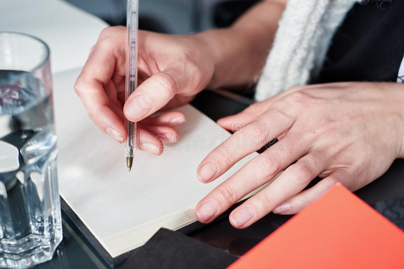 Young woman or student working and writing on paper notebook, using smart phone. Close up of woman`s hands making notes. royalty free stock image