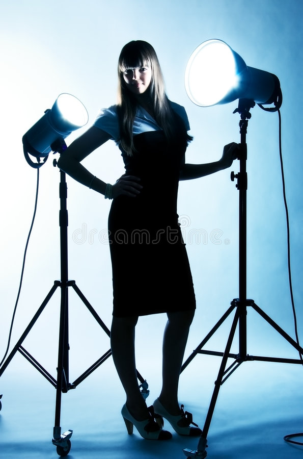 Young woman with studio flashes. Blue tint royalty free stock photography