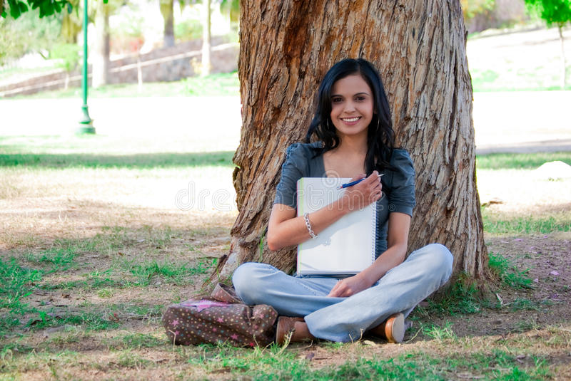 Young woman studying at the park. Young woman holding a notebook and smiling next to a tree at a park stock photography