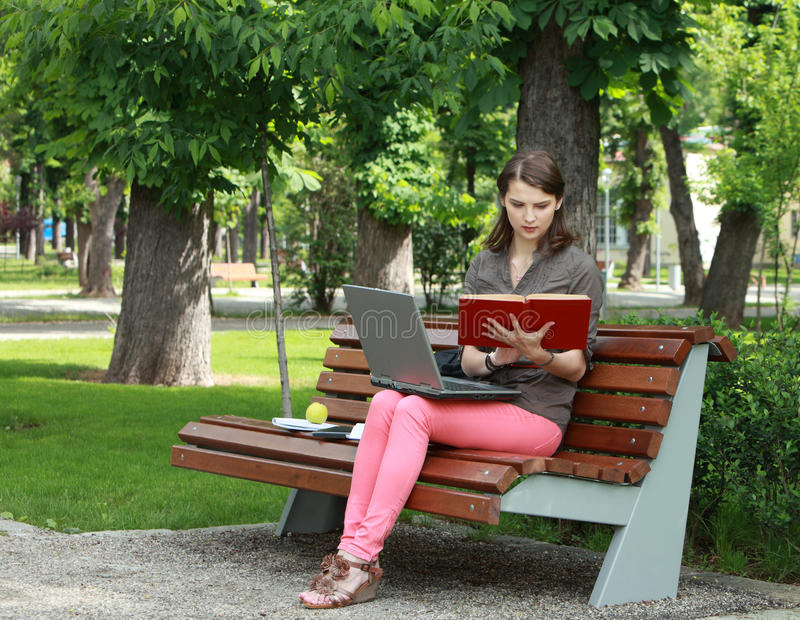Young Woman Studying in a Park royalty free stock image